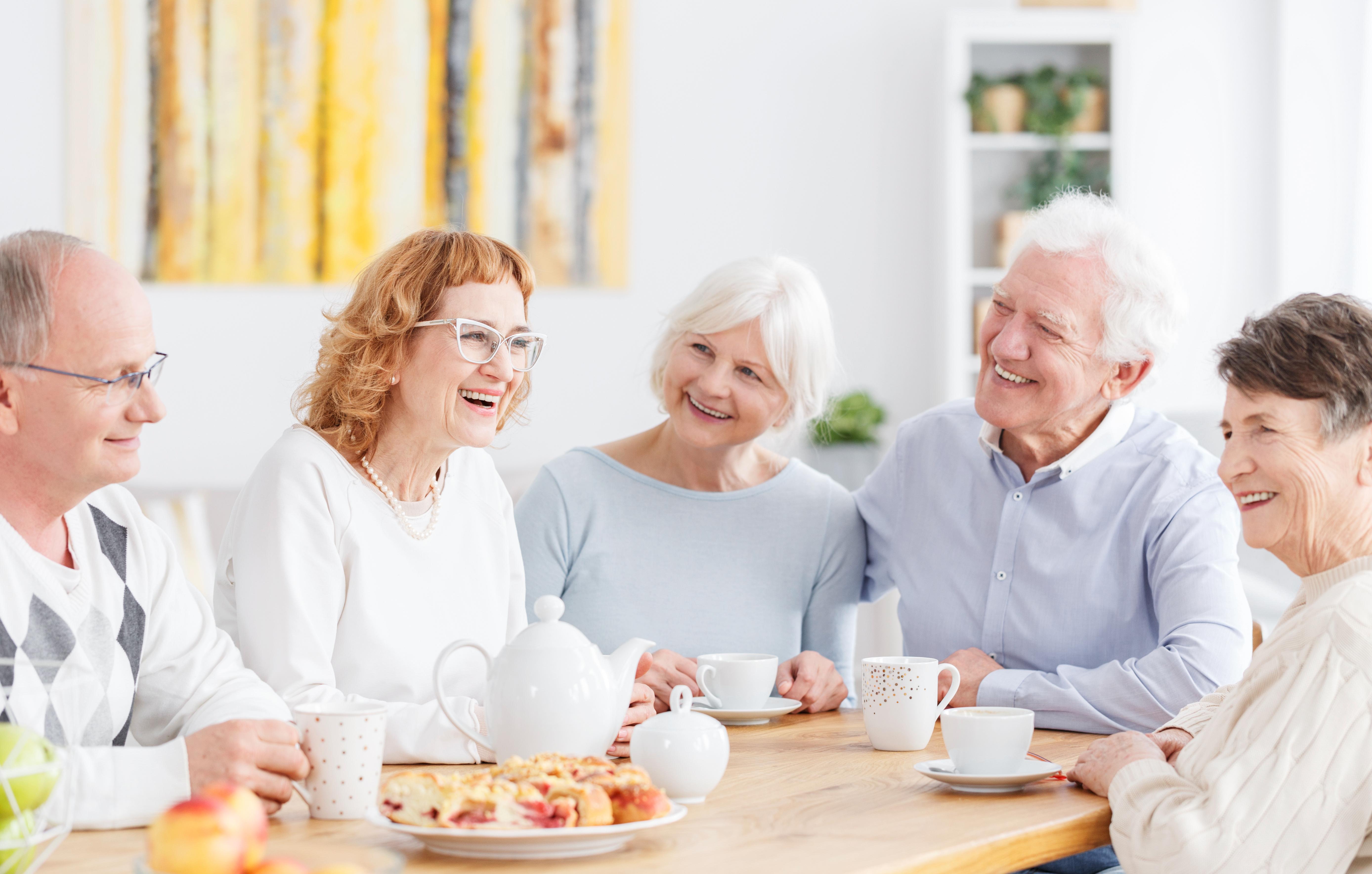 Zajęcia dla seniorów - grupa uśmiechniętych starszych osób na spotkaniu.